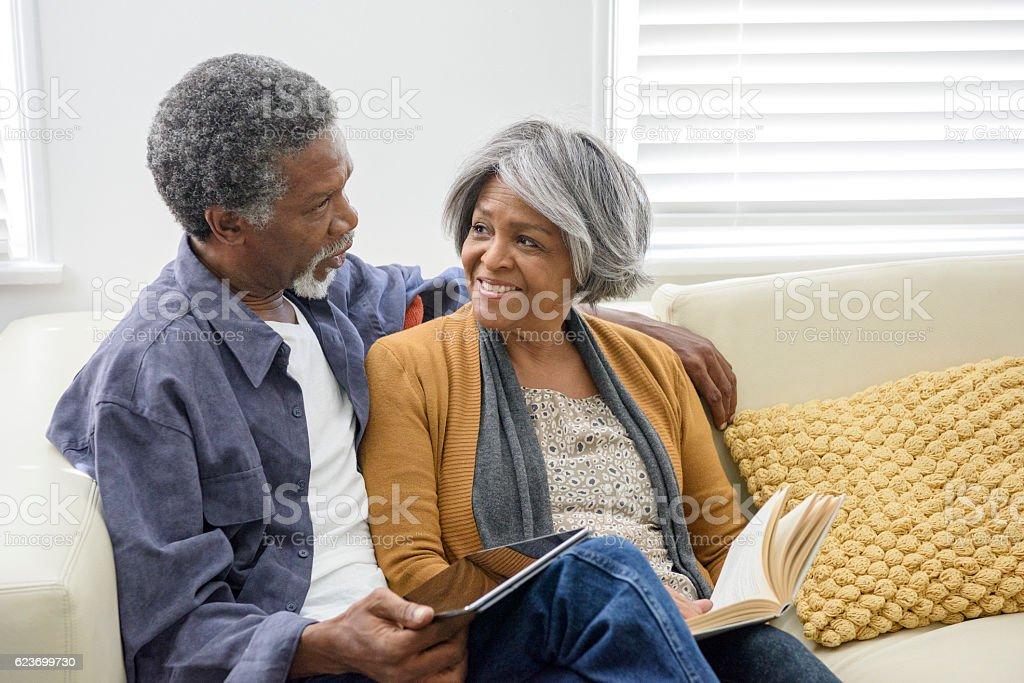 Senior African American couple on sofa smiling affectionately stock photo
