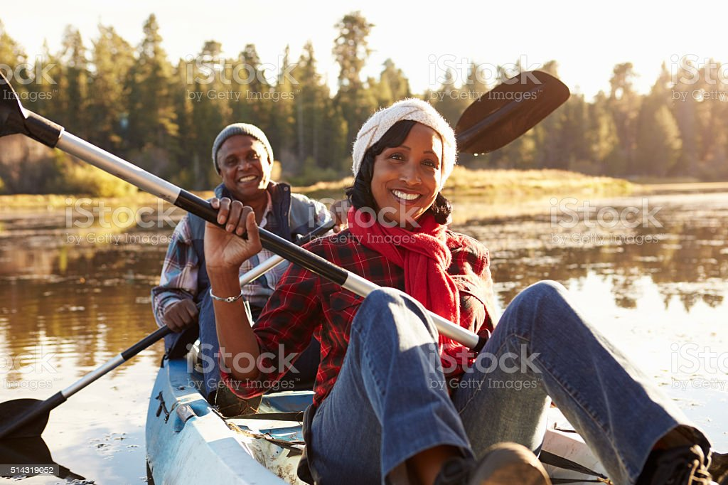 Senior African American Couple Rowing Kayak On Lake stock photo
