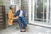 Senior African American couple sitting on porch with drinks