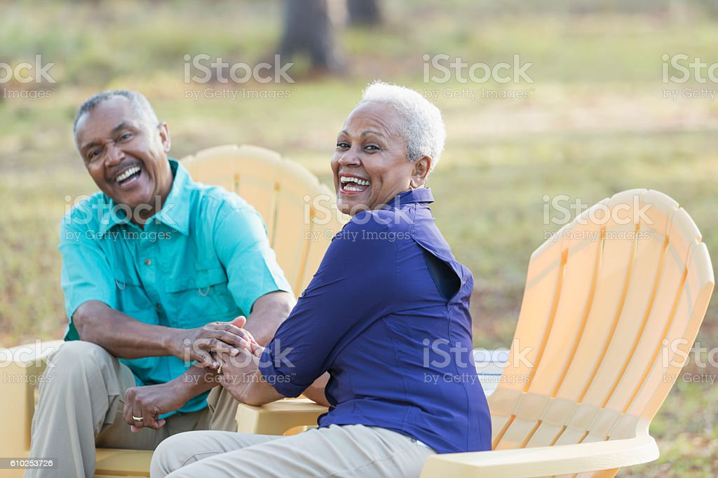 Senior African American couple sitting outdoors laughing stock photo