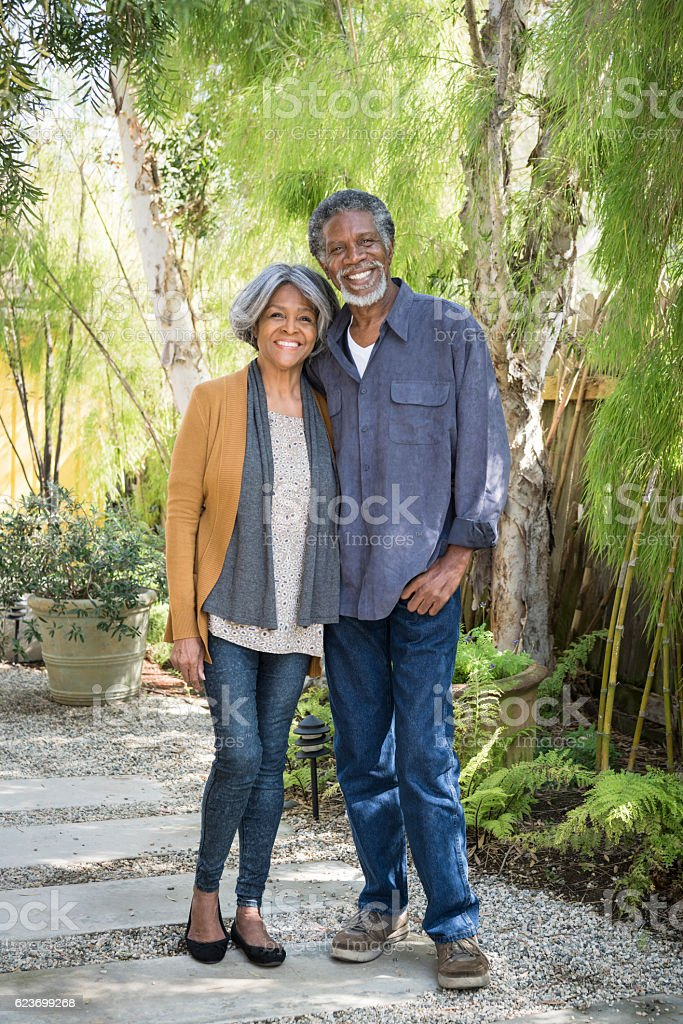 Senior African American couple standing on garden path, smiling stock photo