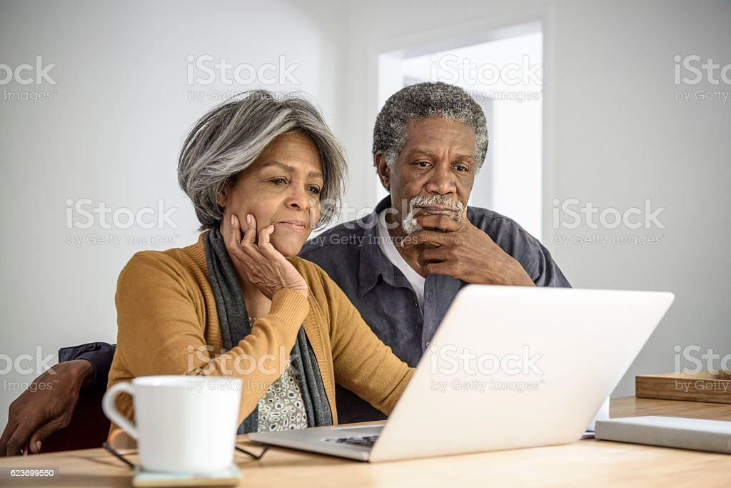 Senior African American couple using laptop, contemplating stock photo