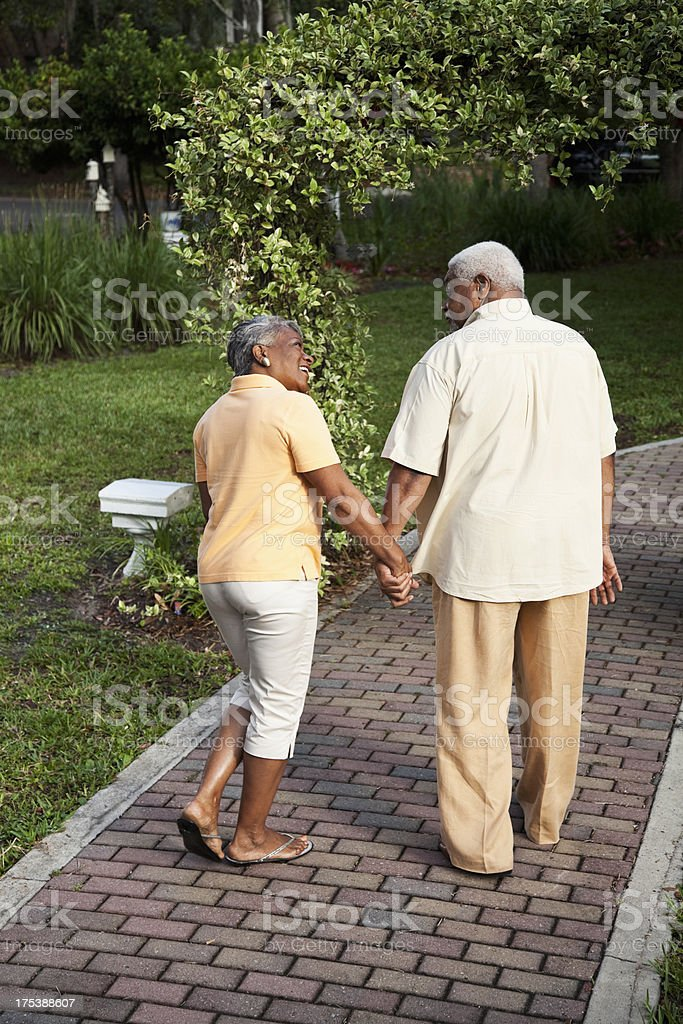 Senior African American couple walking, holding hands stock photo