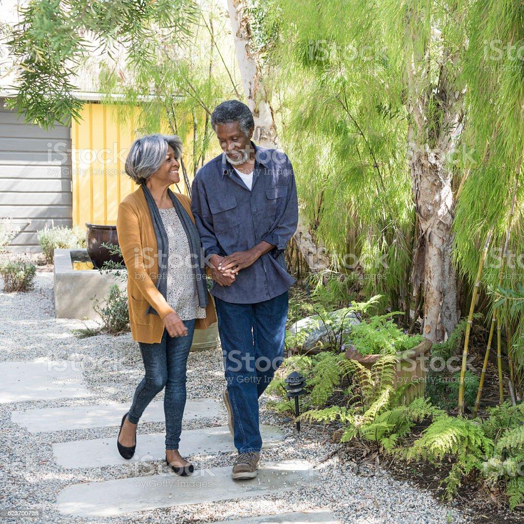 Senior African American couple walking on garden path stock photo