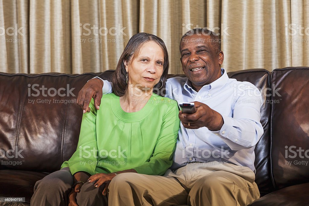 Senior African American couple watching TV on home on couch stock photo