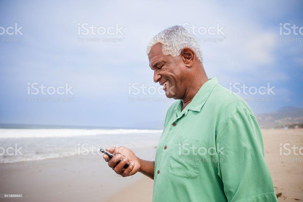Senior African American Man Checking Smartphone stock photo