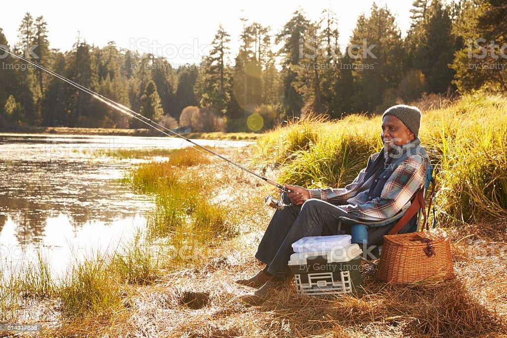 Senior African American Man Fishing By Lake stock photo