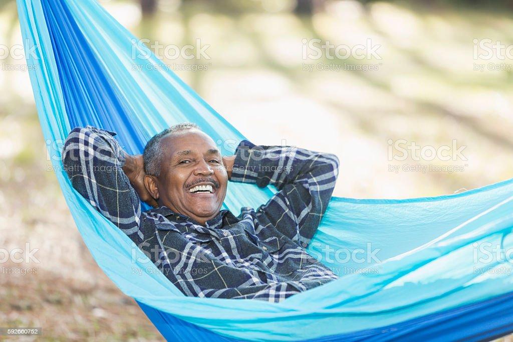 Senior African American man lying in hammock stock photo