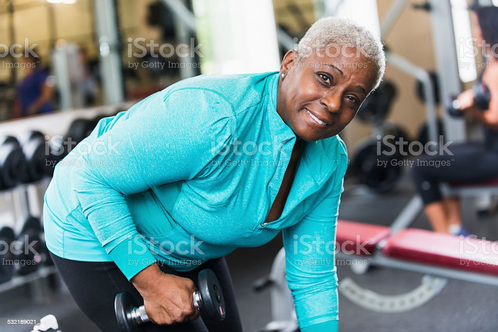 Senior African American woman at gym lifting weights stock photo