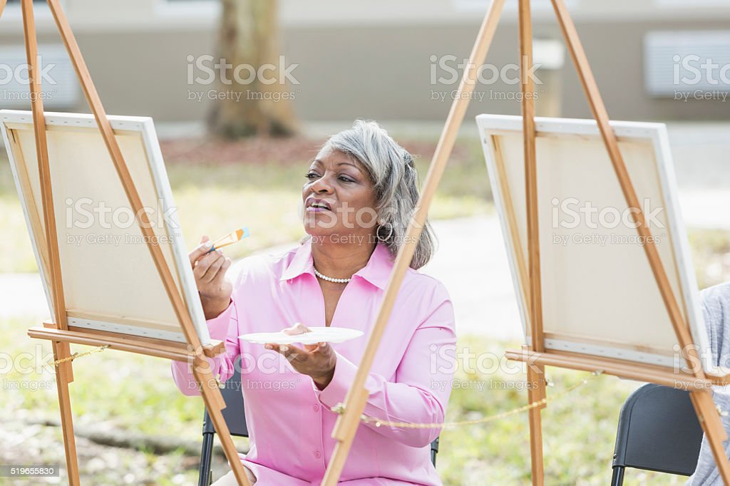 Senior African American woman painting on canvas stock photo