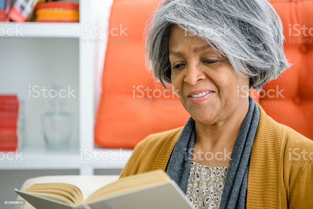 Senior African American woman reading a book stock photo