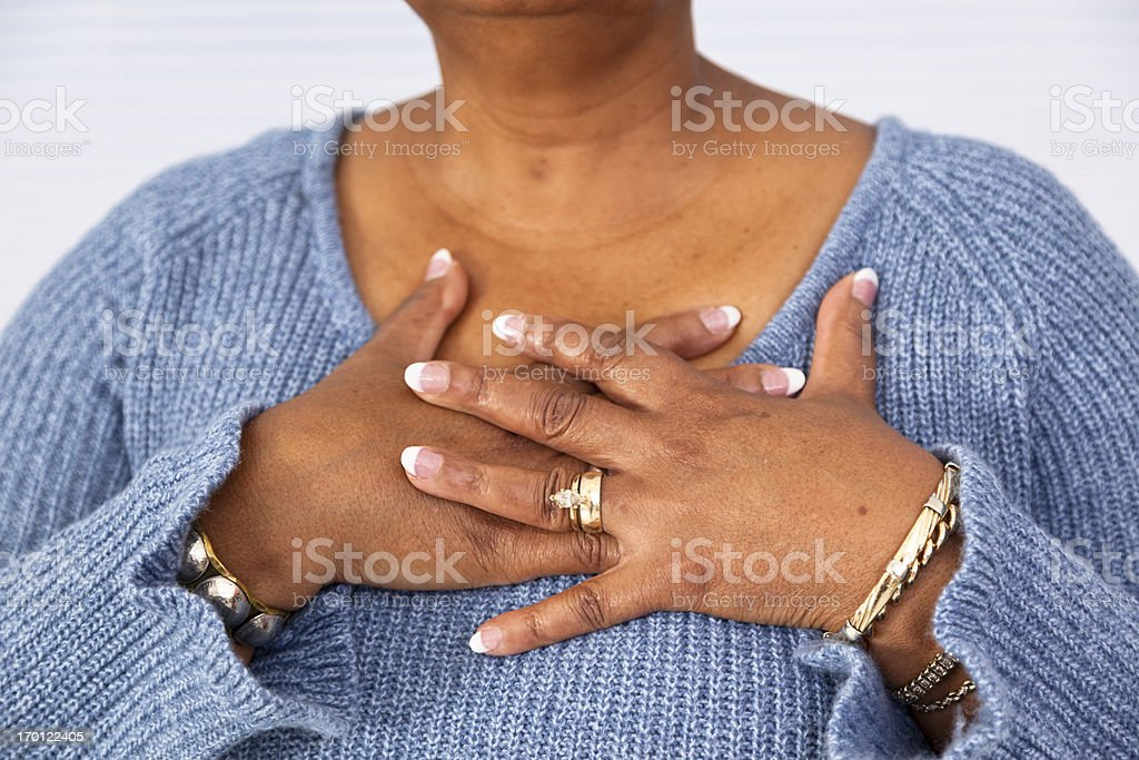 Senior African descent woman clutches chest in pain stock photo