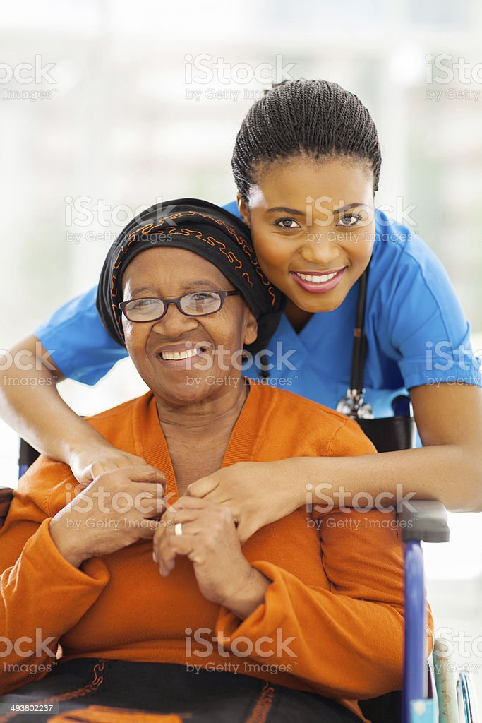 senior african disabled woman caregiver stock photo