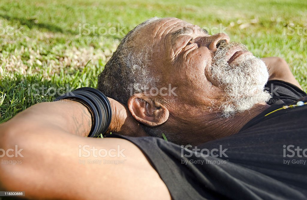 Senior African man relaxing in the sun stock photo