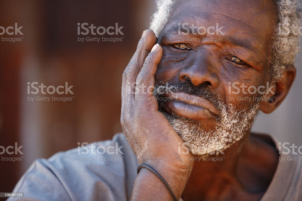 Senior African man resting chin on hand stock photo