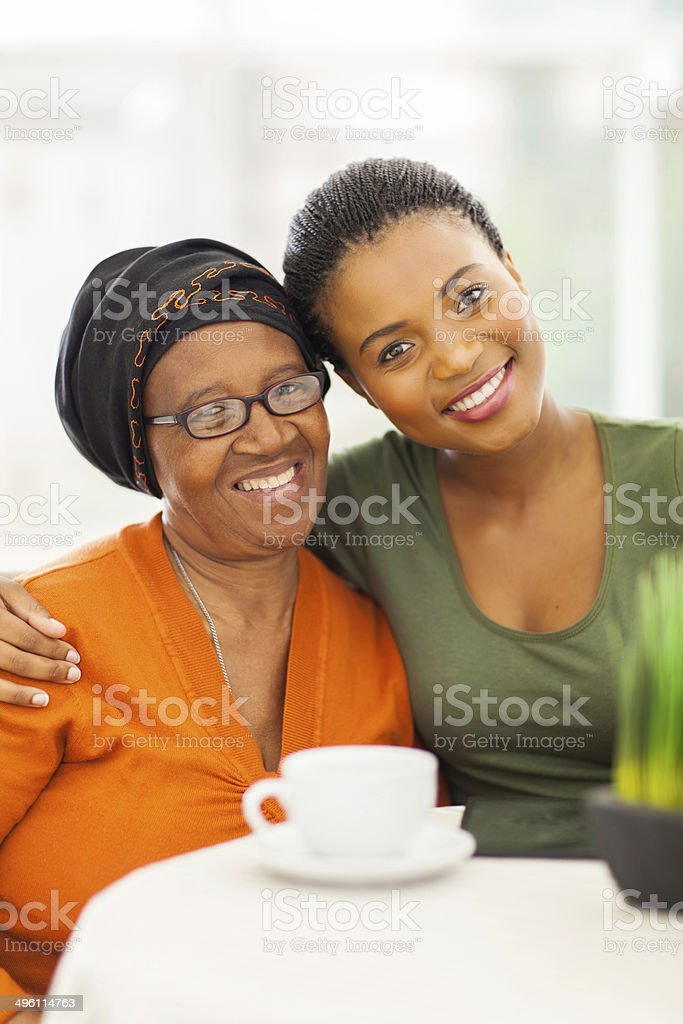 senior african woman with daughter at home stock photo