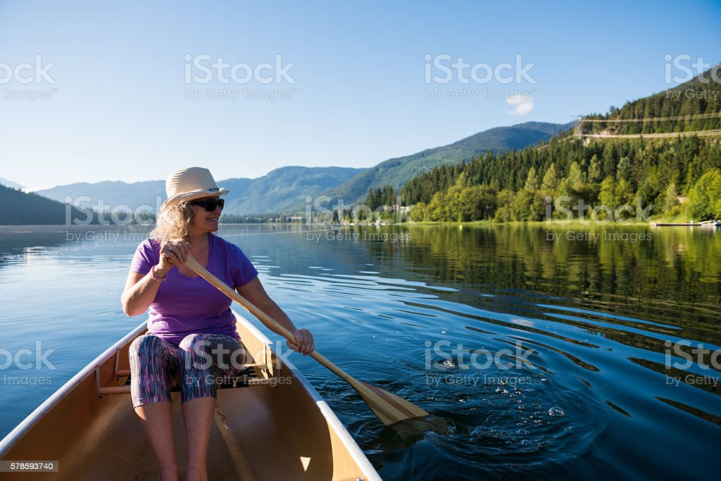 Senior aged woman canoeing on a pristine lake stock photo