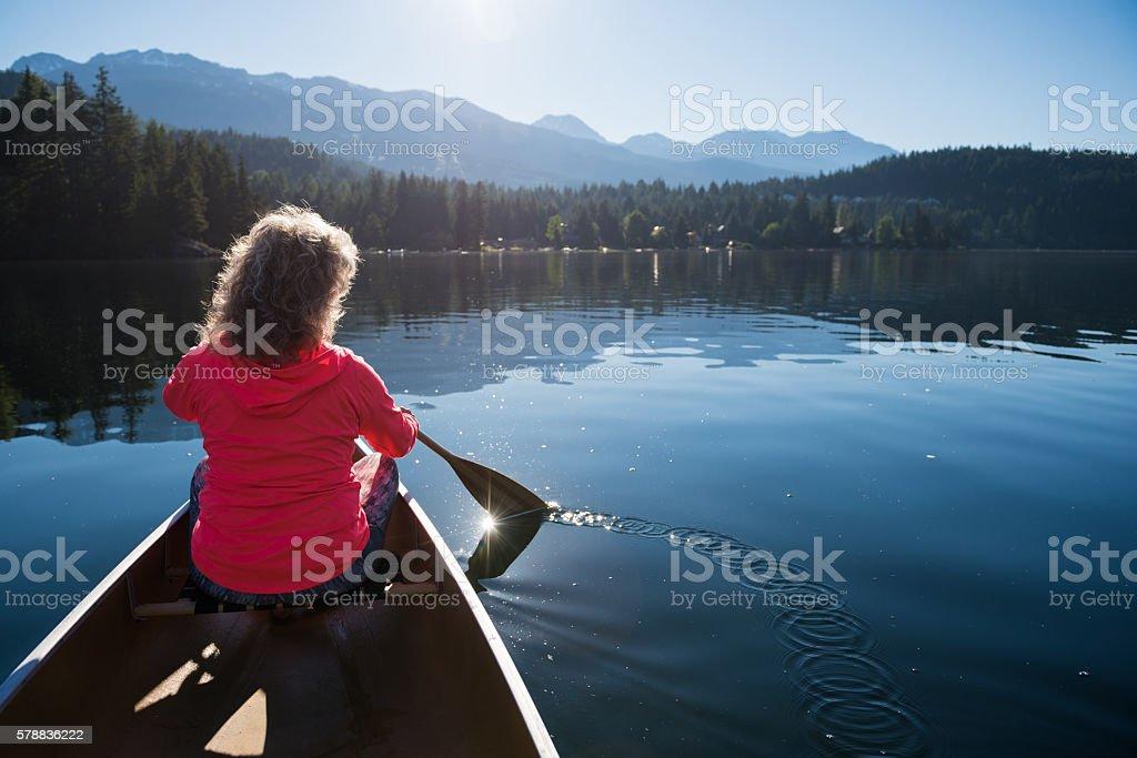Senior aged woman canoeing on a pristine lake stock photo