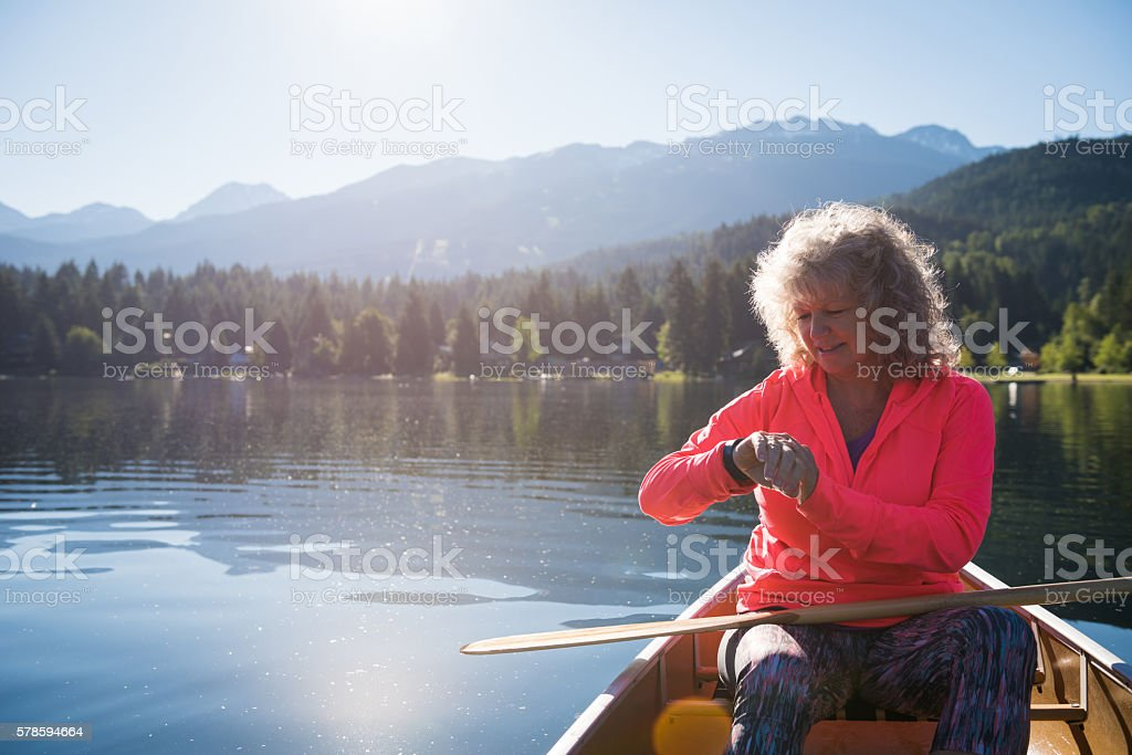 Senior aged woman using a fitness watch stock photo