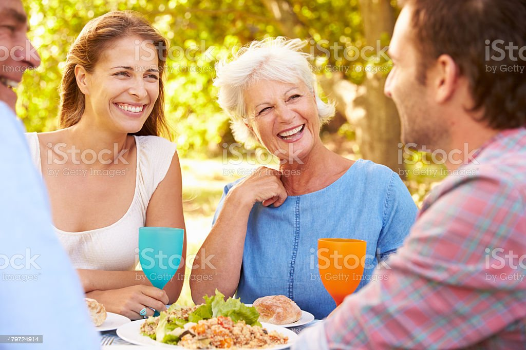 Senior and a young adult couple eating together outdoors stock photo