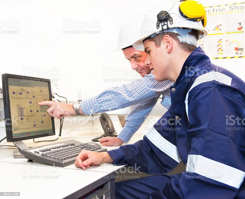 Senior and junior engineers discussing work together in office stock photo
