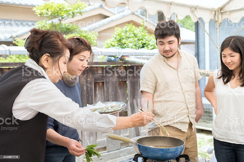 Senior and Mature Japanese Women Teaching Cooking to Young People stock photo