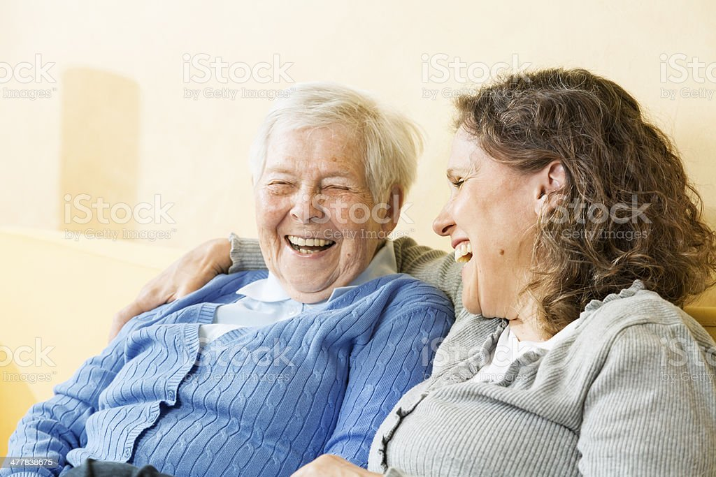 senior woman and mature woman/caregivier, sitting on sofa and...