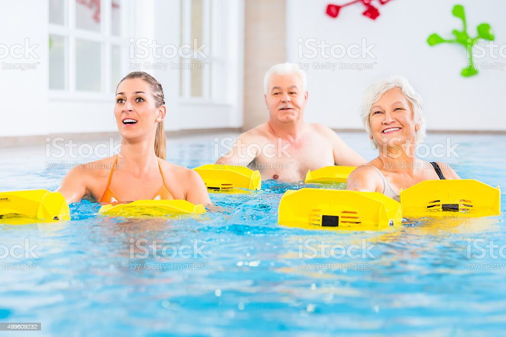 Senior and young people in water gymnastics stock photo