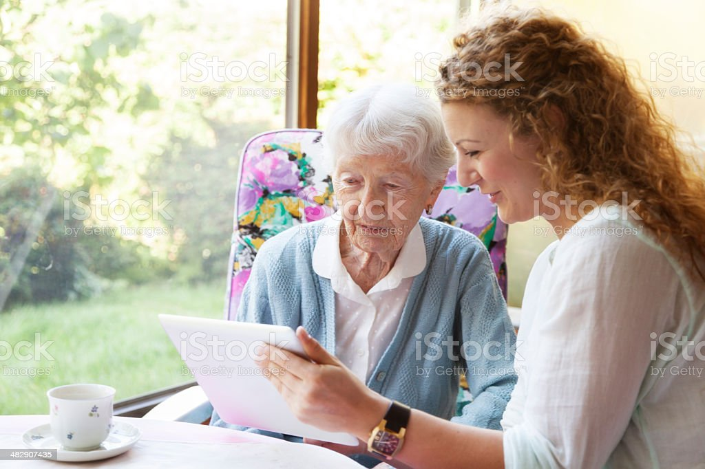 senior and young woman digital tablet stock photo