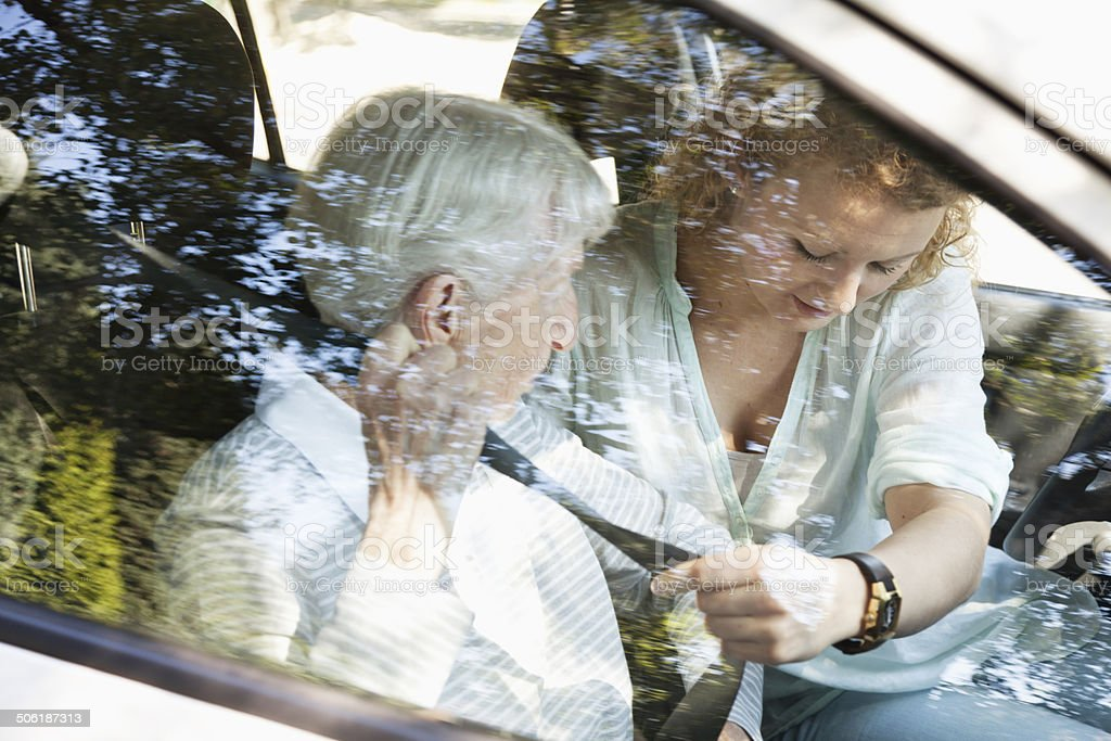 senior and young woman fastening seat belt for safety stock photo
