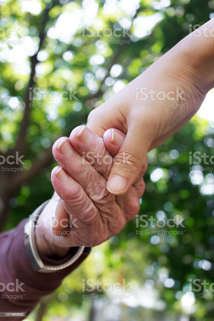 Senior and young women holding hands royalty-free stock photo