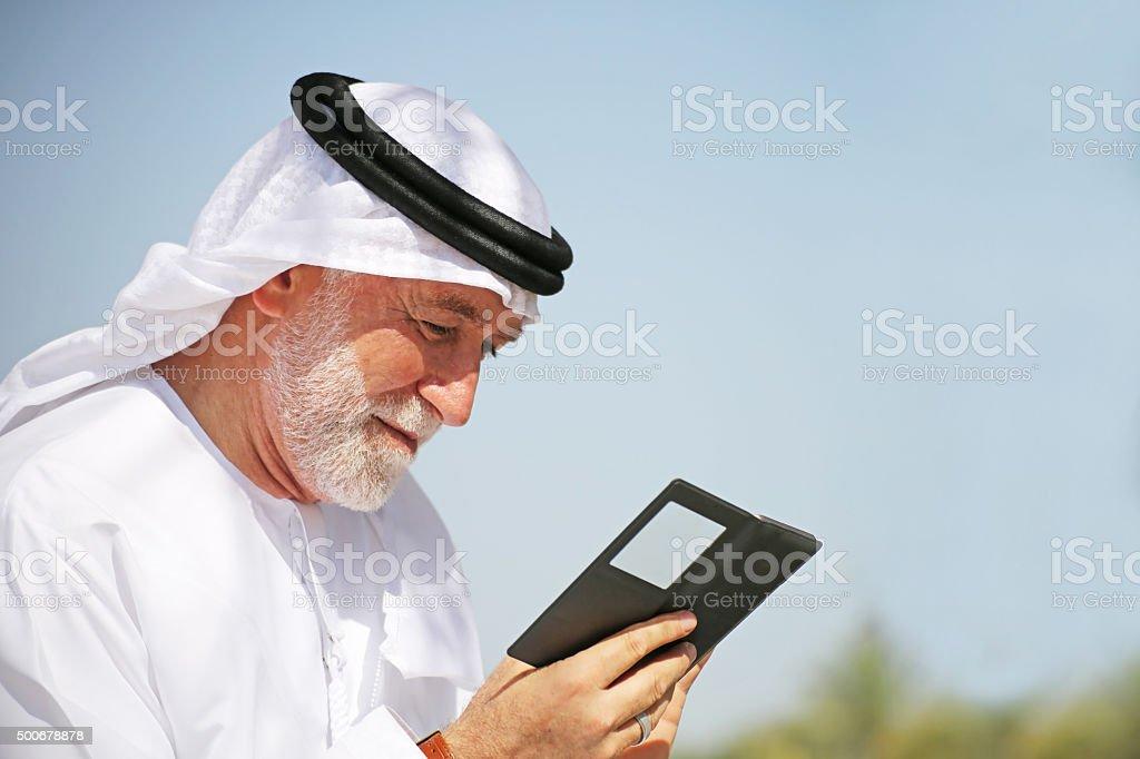 Senior Arab man looking at mobile phone