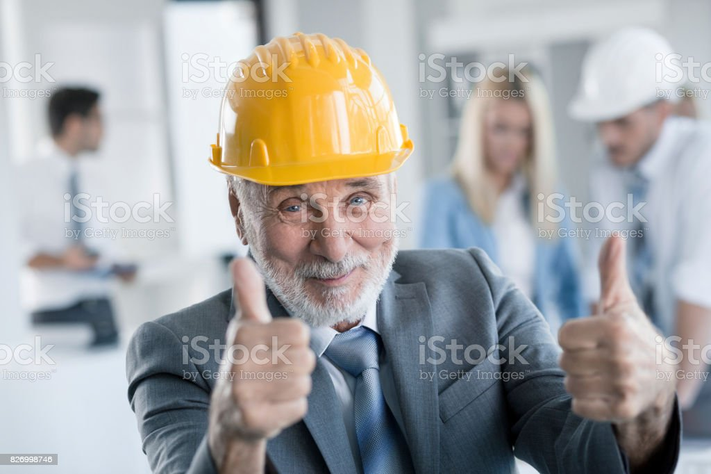 Senior architect showing thumbs up at office stock photo