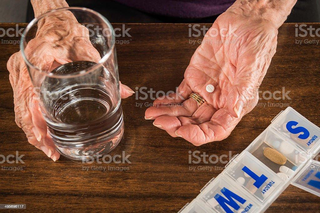 senior arthritis hands, pill medicine organizer, water glass stock photo
