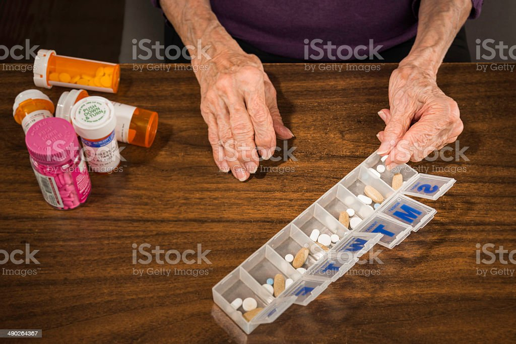 Senior arthritis hands putting pills in 7-Day pill organizer stock photo