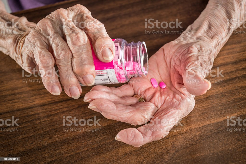senior arthritis hands with pill bottle and medicine tablets stock photo
