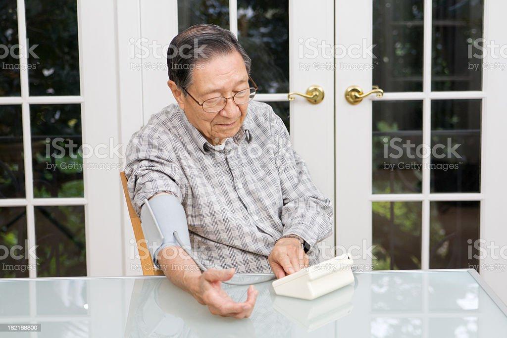 Senior Asian Chinese Man Using Blood Pressure Gauge at Home royalty-free stock photo