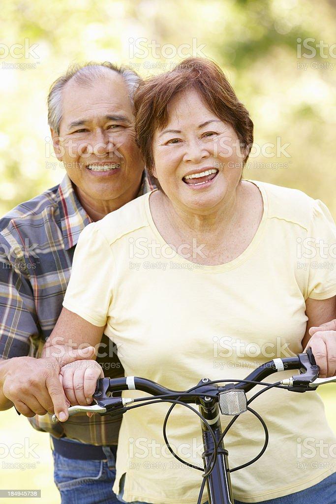 Senior Asian couple both sitting on one bike in park royalty-free stock photo