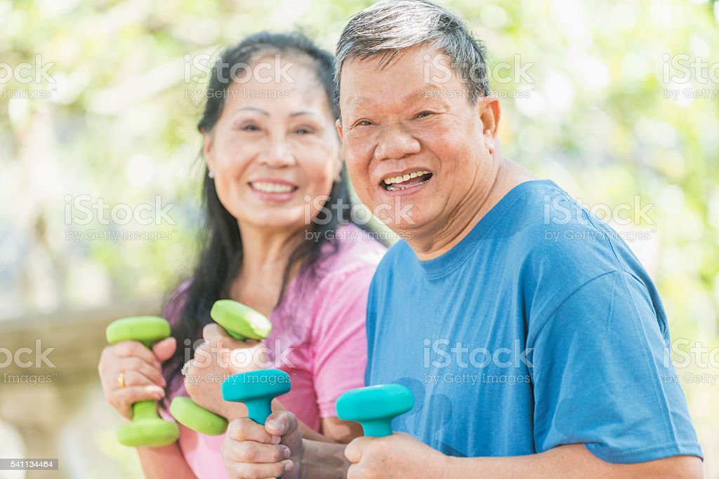 Senior Asian couple exercising outdoors, focus on man stock photo