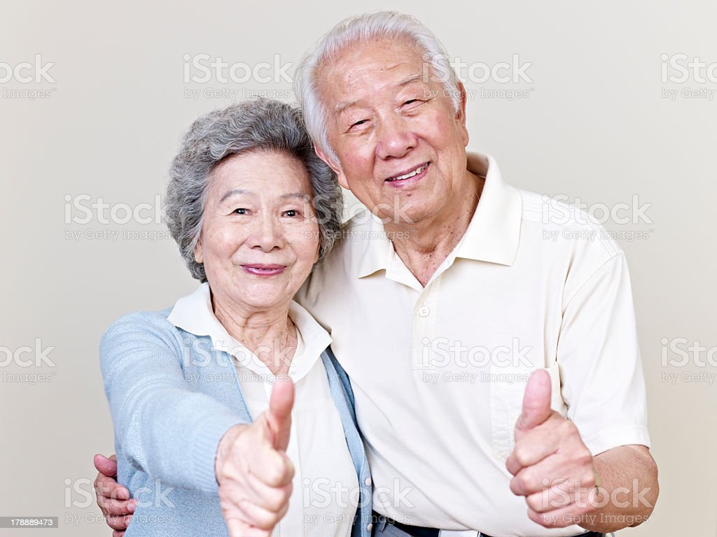 Senior Asian couple giving thumbs-up stock photo