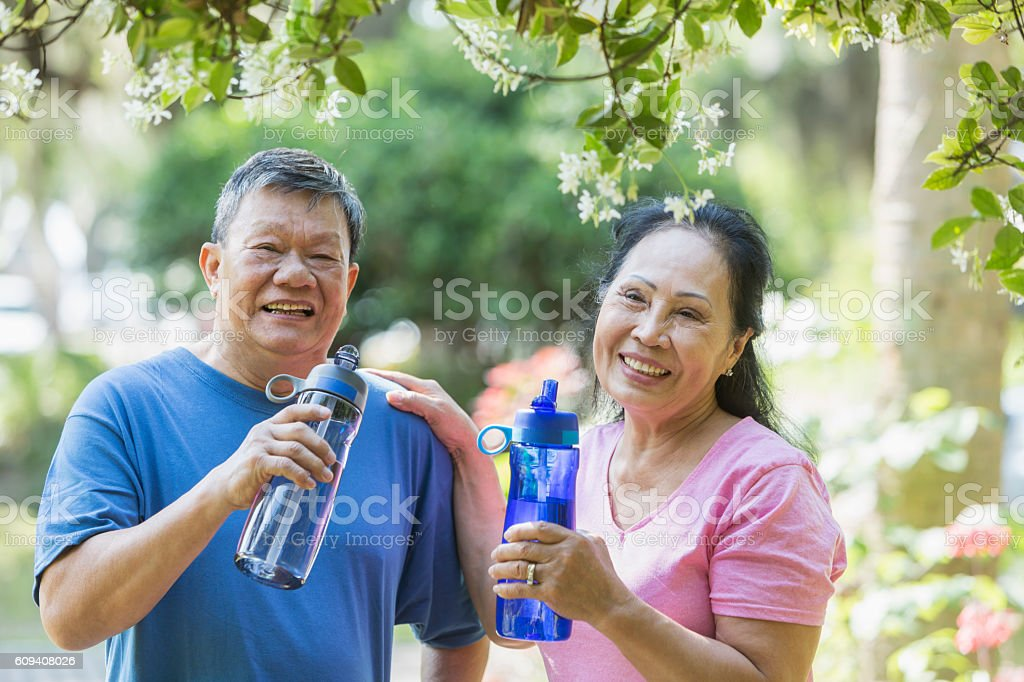 Senior Asian couple in park, drinking water stock photo
