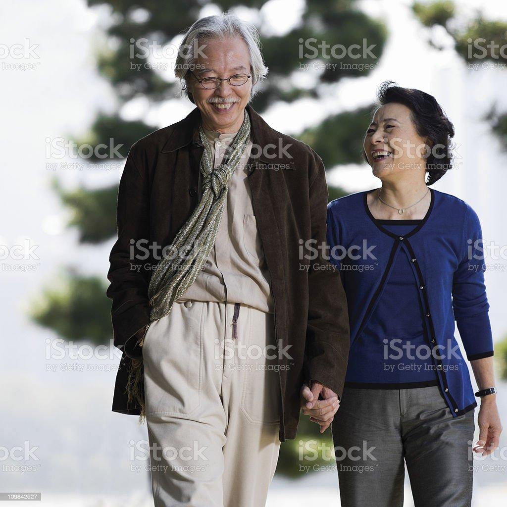 Senior Asian Couple on a Walk Through the Park royalty-free stock photo