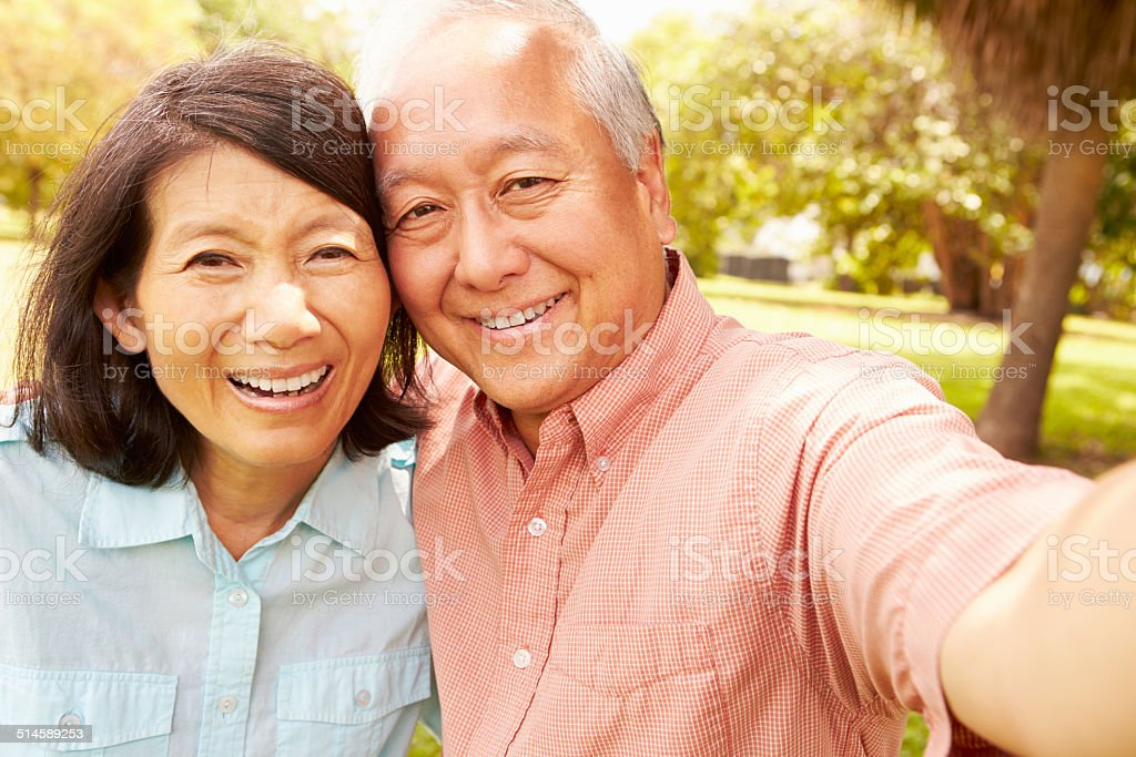 Senior Asian Couple Taking Selfie In Park Together stock photo
