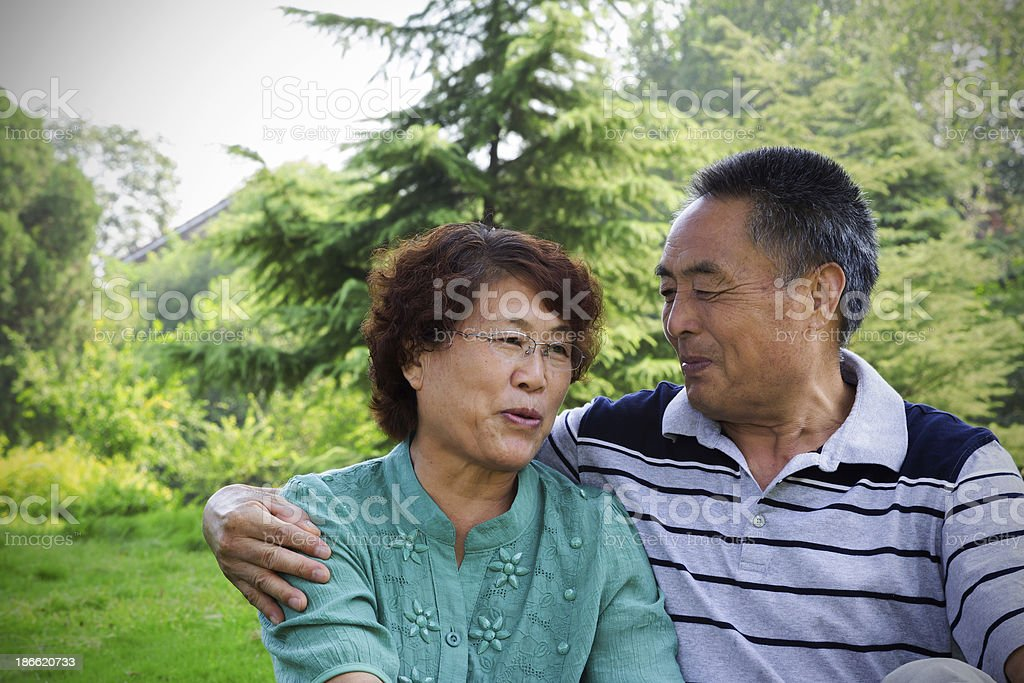 Senior asian couple talking in park royalty-free stock photo
