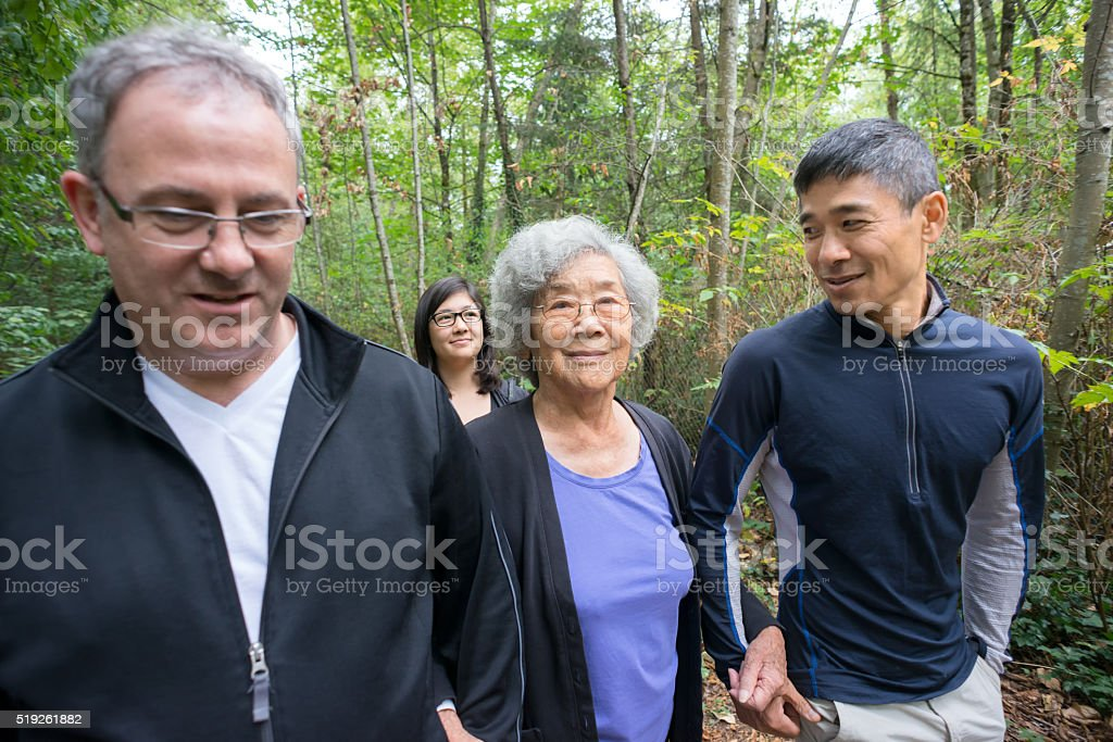 Senior Asian Grandmother Walking in Forest with Son, Daughter, Family stock photo