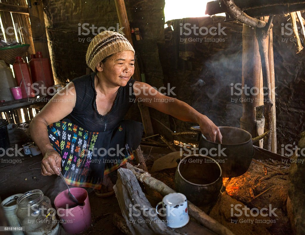 Senior Asian lady cooking with wood fire stock photo