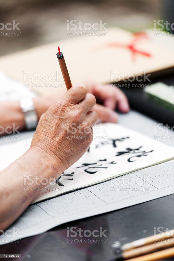 Senior Asian Man doing calligraphy stock photo