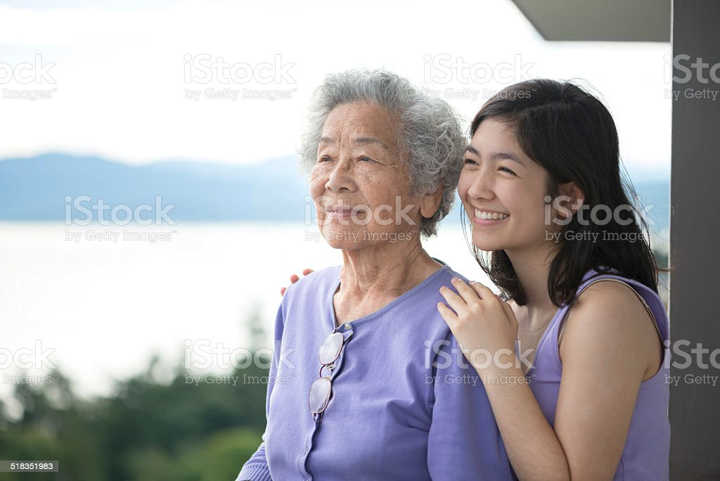Senior Asian Woman and Granddaughter Enjoying View from Balcony stock photo