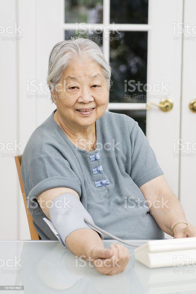 Senior Asian Woman Diabetes Patient Measuring Blood Pressure at Home royalty-free stock photo