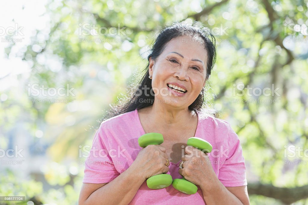 Senior Asian woman lifting handweights stock photo
